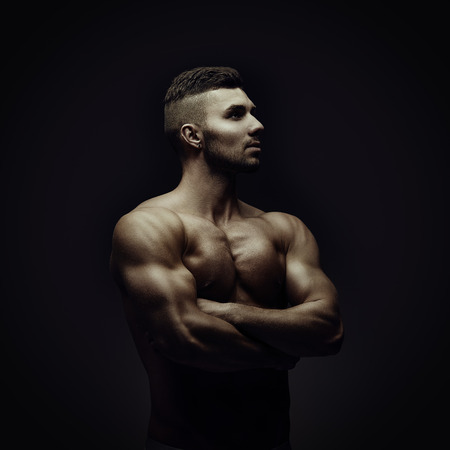 Young athletic brutal man on black background