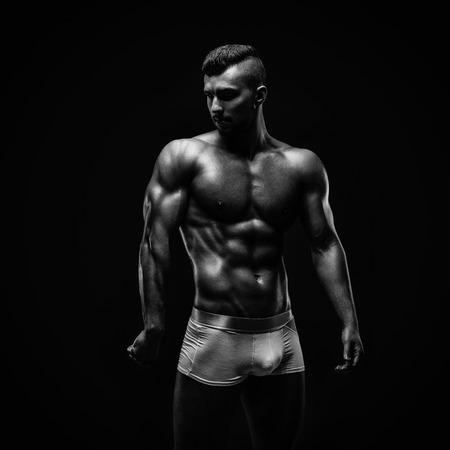 male model: Young athletic brutal man on black background