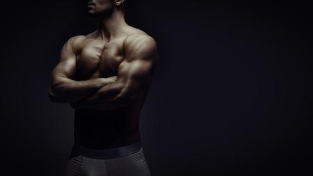 Jeune homme brutal athlétique sur fond noir Banque d'images