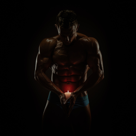 jacked: Artistic portrait of young muscular man with candle Stock Photo