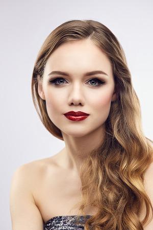 Retrato de la manera de la mujer joven rubia con labios rojos y uñas. Poca profundidad de campo