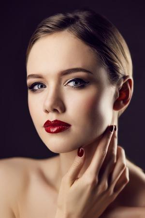 Fashion Portrait der wunderschönen blonden jungen Frau mit roten Lippen und Nägel. Geringe Schärfentiefe. Dunkler Hintergrund