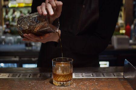 Pouring prepared cocktail into glass Archivio Fotografico