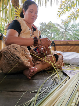 Indigenous tribe woman weaving nipa leaves Reklamní fotografie