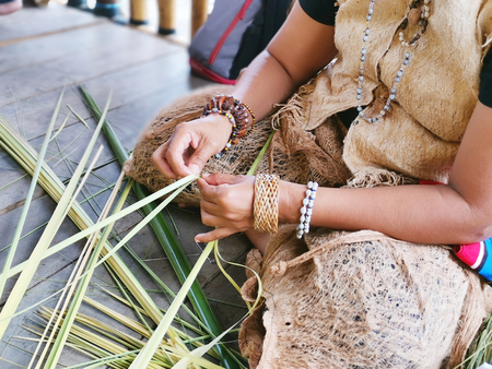 Indigenous tribe woman weaving nipa leaves Imagens