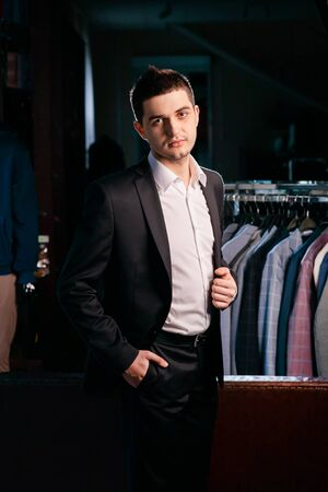 Confident cheerful man in showroom of men business clothes store. Dressing room. Foto de archivo