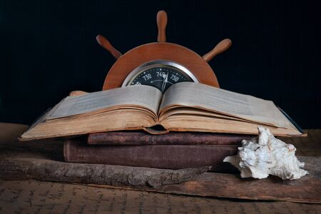 open old book, ship steering wheel and white shell on a wooden table. The concept of seafaring, education and knowledge.