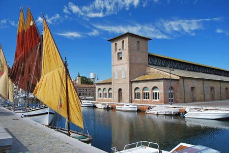 ships on the canal near sea and old salt building in Cervia
