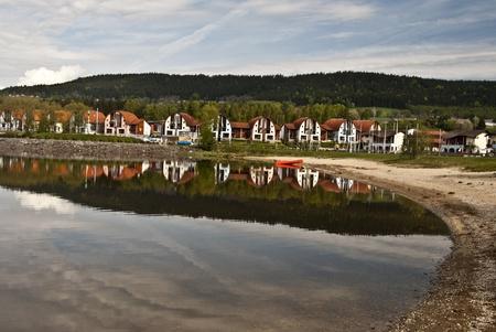 lipno: Lipno river dam, sandy beach, recreational buildings and hill with blue sky
