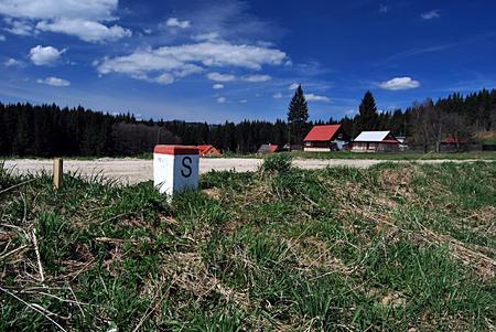 boundaries: boundary marker on slovak-czech boundaries with hamlets of Konecna settlement on the background