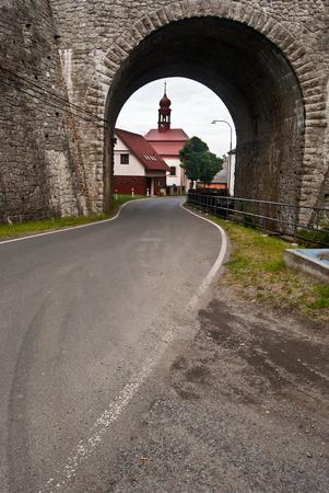 bellow: road bellow railway bridge with church in Svor village Stock Photo