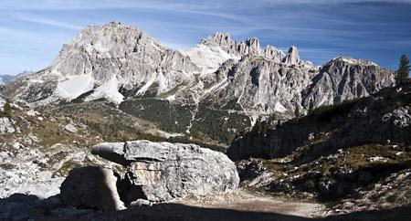 frontyard: panorama of Laguazoi and Tofana mountain group near Cortina dAmpezzo above Passo Falzarego with big stone on the frontyard during hiking from Passo Falzarego to Monte Nuvolau peak Stock Photo