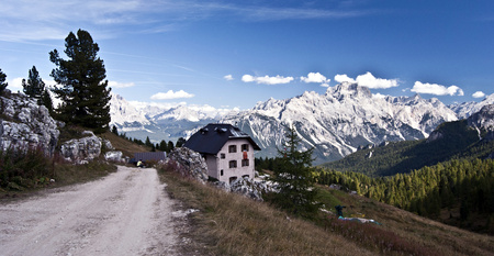 torri: panorama of Rifugio Cinque Torri chalet with foot-path and trees around and peaks of Antelao and Marmarole mountain groups on the background near Cortina dAmpezzo above Passo Falzarego