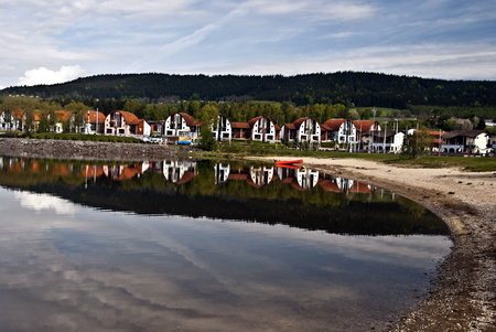 lipno: Lipno resort with recreational houses, sandy beach, Lipno water reservoir, Sumava hills and blue sky with only few clouds in South Bohemia near borders with Austria