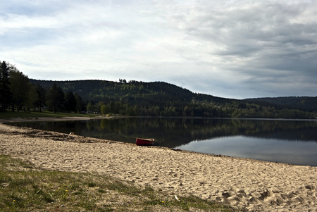 lipno: sandy beach with canoe, Lipno water reservoir, Sumava hills and blue sky with clouds Stock Photo