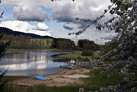 lipno: Lipno water reservoir in South Bohemia with sandy beach with kayak, blossom, hills and blue sky with few clouds Stock Photo