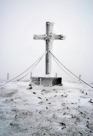 alpen: cross on summit of highest peak of Fischbacher Alpen Stuhleck in Styria near Semmering pass on winter morning with misty and wind