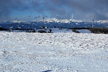 alpen: winter austrian alps panorama with wind turbines on the frontyard during snowshoeing in Fischbacher Alpen mountains in Styria