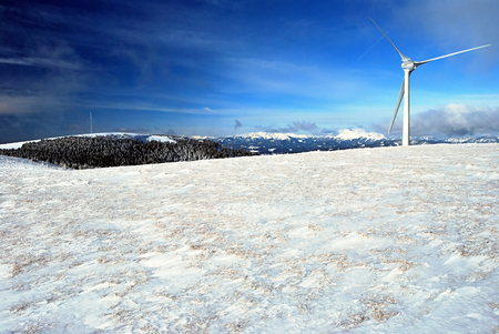 alpen: winter austrian alps panorama with wind turbine, Admunsenhohe hill in Fischbacher Alpen and higher peaks on the background and blue sky in Styria