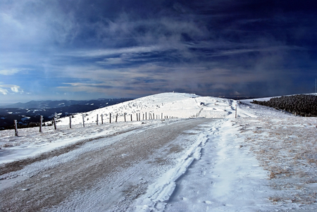 winter hiking trail in Fischbacher Alpen in Styria with blue sky
