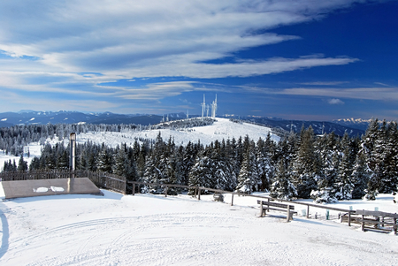 alpen: winter Fischbacher Alpen mountains panorama with hills, wind turbines and blue sky from Roseggerhaus chalet above Murzzuschlag city in Styria