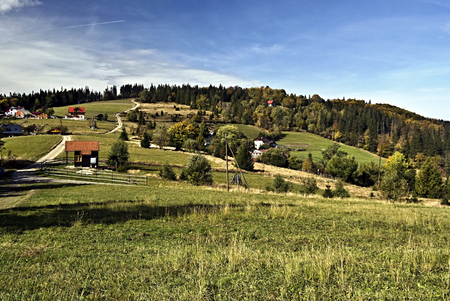 hamlets: Beskid Slaski mountains with Cieslar hill, mountain meadow, trees, hamlets and blue sky Stock Photo