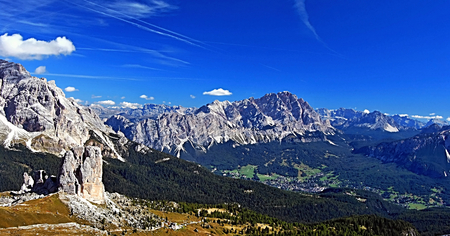 mountain valley: mountain valley with Cortina dAmpezzo with peaks around in autumn Dolomites mountains with blue sky and only few clouds Stock Photo