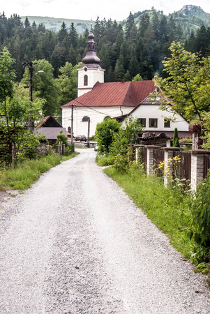 stare: church with road in Stare Hory village with Majerova skala rocky hill in Velka Fatra mountains on the background
