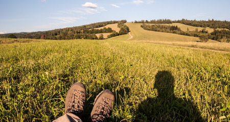 hiking boots: hiking boots on meadow, photographer shadow and blue sky in evening Kysucke Beskydy mountains above Oscadnica near Cadca city in Kysuce region