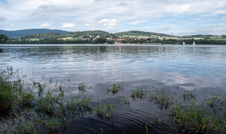 lipno: Lipno water reservoir with sails and Horni Plana village with hills of Sumava mountains around
