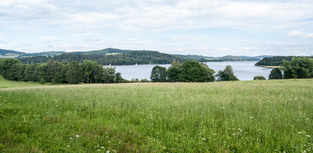 lipno: meadow and Lipno water reservoir with sails near Horni Plana in South Bohemia in Sumava mountains