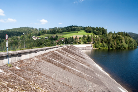 diversion: diversion dam of Jezioro Czernianskie water reservoir on Wisla river near Wisla resort in Beskid Slaski mountains with small hill on the background and blue sky with only few clouds Stock Photo