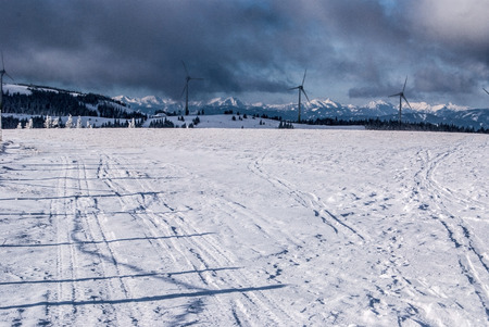 alpen: winter austrian alps panorama with snow, wind turbines farm, mountain peaks and blue sky with clouds from Grazer Stuhleck hill in Fischbacher Alpen mountains in Styria