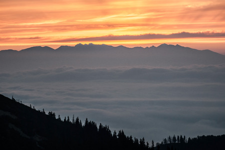 mala fatra: daylight with colorful sky above Tatras mountain range from Chata pod Chlebom chalet in Mala Fatra mountains in Slovakia Stock Photo