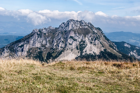 mala fatra: rocky limestone and olomitian Velky Rozsutec hill from mountain meadow on Stoh hill summit in autumn Mala Fatra mountains in Slovakia with blue sky and clouds Stock Photo