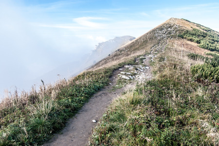 mala fatra: hiking trail to Hromove hill in autumn Mala Fatra mountains with blue sky and fog bellow