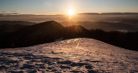 mala fatra: sunrise above winter mountains with snow, clear sky and misty in valleys from Revan hill above Fackovske sedlo in southernmost part of Mala Fatra mountains in Slovakia