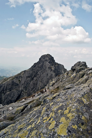 orla: sharp Kozi Wierch peak on famous and difficult Orla Perc hiking trail in polish part of High Tatras mountains during summer day with blue sky and clouds Stock Photo