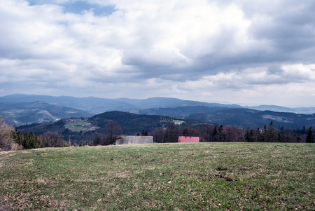 hamlets: view from Cieslar hill on polish - czech borders in Silesian Beskids mountains with mountain meadow, isolated houses, hamlets and hills during nice spring day with blue sky and clouds