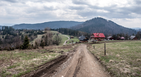 nice landscape of Silesian Beskids mountains on polish - czech borders bellow Cieslar hill with dirty road, isolated houses, meadow, foresta and hills