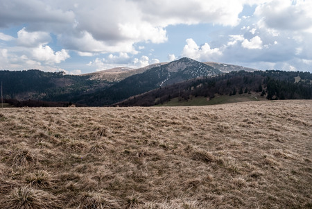carpathians: panorama of spring Velka Fatra mountains near Chyzky guidepost in Liptov region in Slovakia with mountain meadow, hills with small snow fields and blue sky with clouds Stock Photo