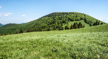 Osnica hill covered by forest and meadows with meadow on Medziholie pass bellow and blue sky in Mala Fatra mountains in Slovakia