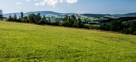 mountain countryside with meadows, fields, villages, trees, hills and blue sky with clouds on bohemian - moravian borderland near Kraliky city in Czech republic