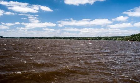 windy Velke Darko pond with wavesm sailboats and blue sky with clouds on Ceskomoravska vrchovina near Zdar nad Sazavou  in Czech republic