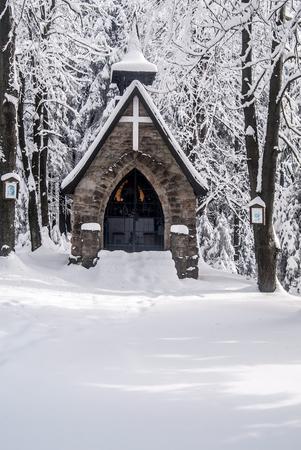 stone chapel with snow and ftozen forest around on Bily kriz in Moravskoslezske Beskydy mountains ion czech - slovakian borders