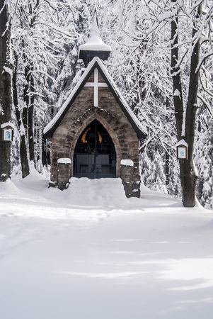 stone chapel with snow and ftozen forest around on Bily kriz in Moravskoslezske Beskydy mountains ion czech - slovakian borders