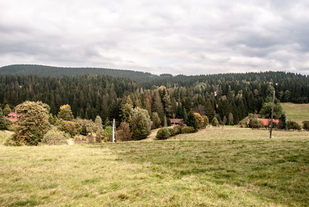 autumn mountain countryside with meadow, few houses, trees and hills covered by forest near Vysni Mohelnice settlement bellow Lysa hora hill in Moravskoslezske Beskydy mountains in Czech republic Foto de archivo