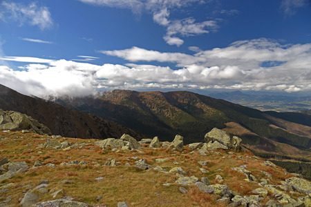 view from hiking trail bellow Chopok mountain peak in Nizke Tatry mountains in Slovakia with hills, meadow and stones during autumn day with blue sky and clouds
