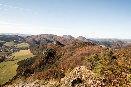 View from Stefanikova vyhliadka in Sulovske skaly mountains with hills covered by colorful forest and rural landscape with Sulov village during autumn day with clear sky
