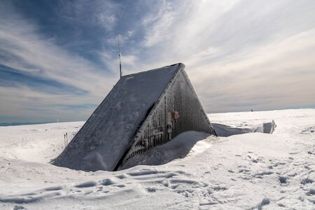 Vysoka hole hill in winter Jeseniky mountains un Czech republic with hut, snow and blue sky with clouds